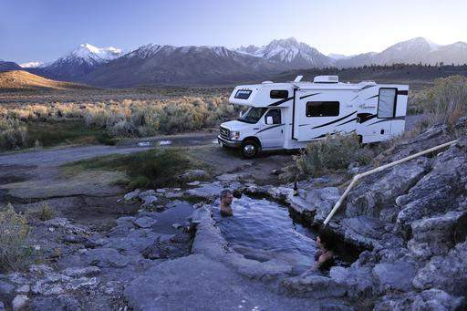 Off the Grid RV'ing. Image of RV camping with two people in a man made hot spring. Image is in full colour with mountains in the background.