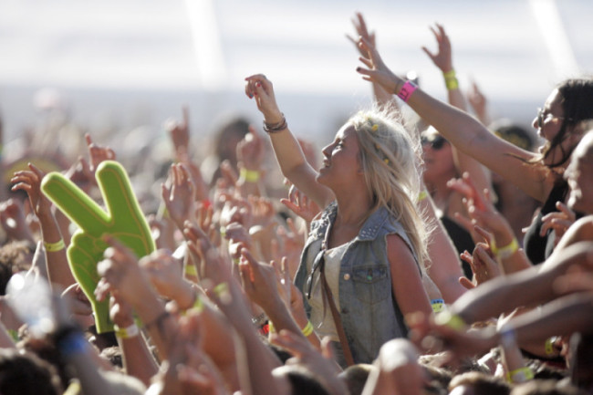 A crowd of people gathered at a music festival with arms raised in the air.