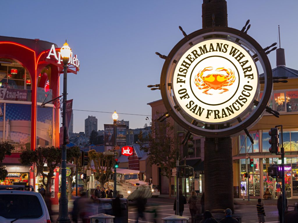 "Fisherman's Wharf San Francisco. Image is a . close up of a public sign saying ""fishermans warf"" in downtown with pedestrians walking around. Image is in full colour."