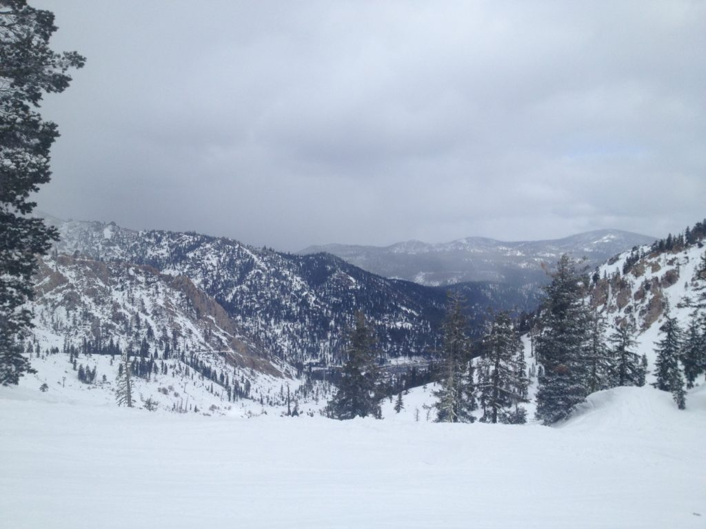 Squaw Valley, image is of snow covered hills with trees covering the mountains. Image is in full colour with a cloudy background.