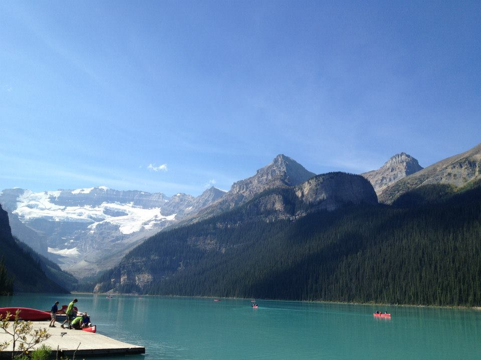 Lake Louise, AB. Image is in full colour of Lake Louise with people canoeing on the lake and mountains in the background.