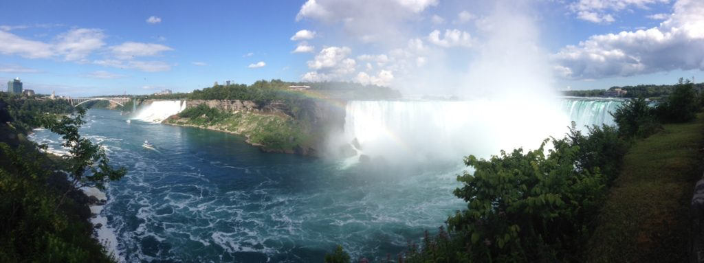 Distance shot of Niagara Falls waterfalls and the river runoff. Image is in full colour.