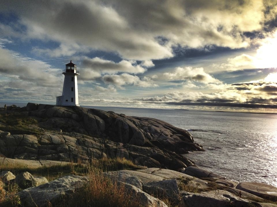 Nova Scotia white lighthouse overlooking the ocean. Image is in full colour.