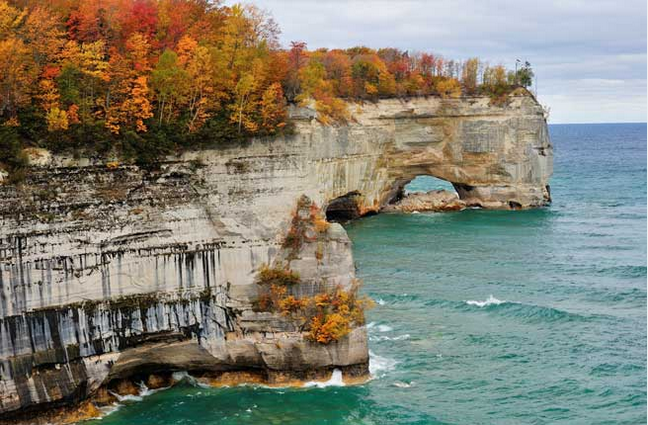 Upper Peninsula Michigan ocean view with cliffs covered in trees on the left side. Image is in full colour.