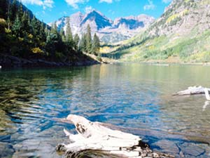 Colorado, Maroon Lake. Image is of the lake viewed from the ground with tree and mountains in the background. Image is in full colour.