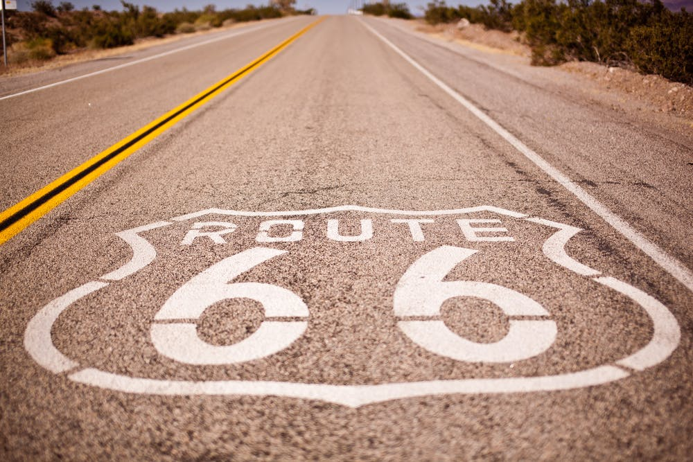 Route 66 sign painted on the highway between Chicago and Los Angeles