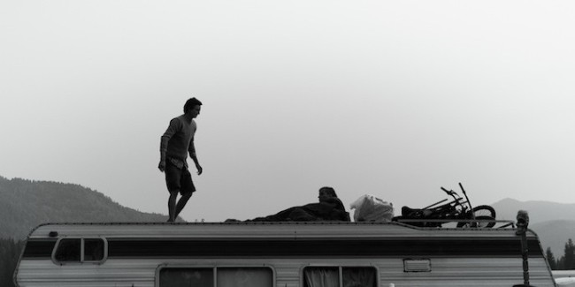 RV'ing at Music Festivals. Man standing on top of an RV. Image is in black and white.